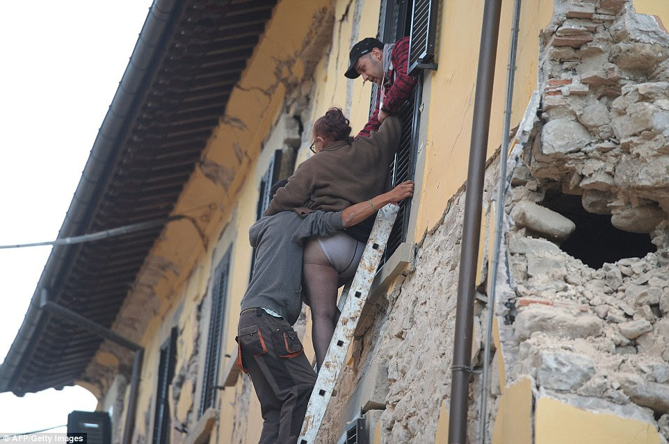 Ajudou a segurança: Uma mulher é realizado por uma escada de sua janela no andar de cima, que tem um buraco na parede