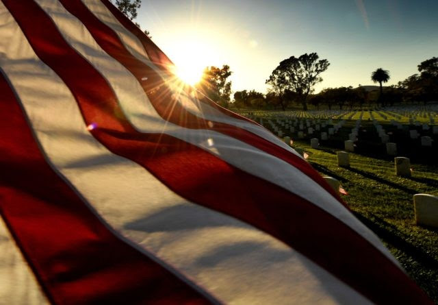 TOPSHOT - The sun sets over a flag at the Los Angeles National Military Cemetery two days before Memorial Day in Los Angeles, California on May 26, 2018. - Memorial Day, which originated after the US Civil War that ended in 1865, is an American holiday honoring the men and …