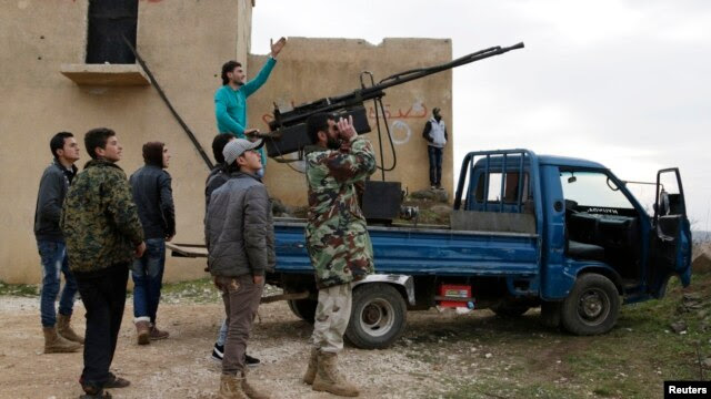 A rebel fighter from the Ahrar al-Sham Islamist movement gestures while standing on a pick-up truck mounted with an antiaircraft weapon, as he looks at the sky with his fellow fighters outside Idlib.
