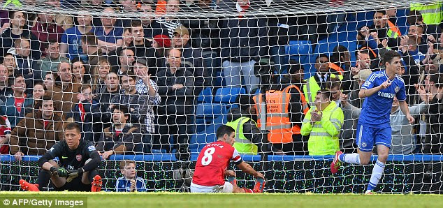 Helpless: Oscar wheels away in celebration as Arsenal fans behind the goal look distraught