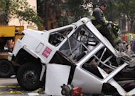 A firefighter leans against the roof of a damaged mini-bus while standing on the beam that fell from a bridge onto the bus during an earthquake, in Mexico City, Tuesday March 20, 2012. A strong 7.4-magnitude earthquake hit central and southern Mexico on Tuesday, collapsing at least 60 homes near the epicenter and a pedestrian bridge in the capital where people fled shaking office buildings. There were no passengers in the mini-bus and the driver suffered minor injuries, according to firefighters. (AP Photo/Alexandre Meneghini)