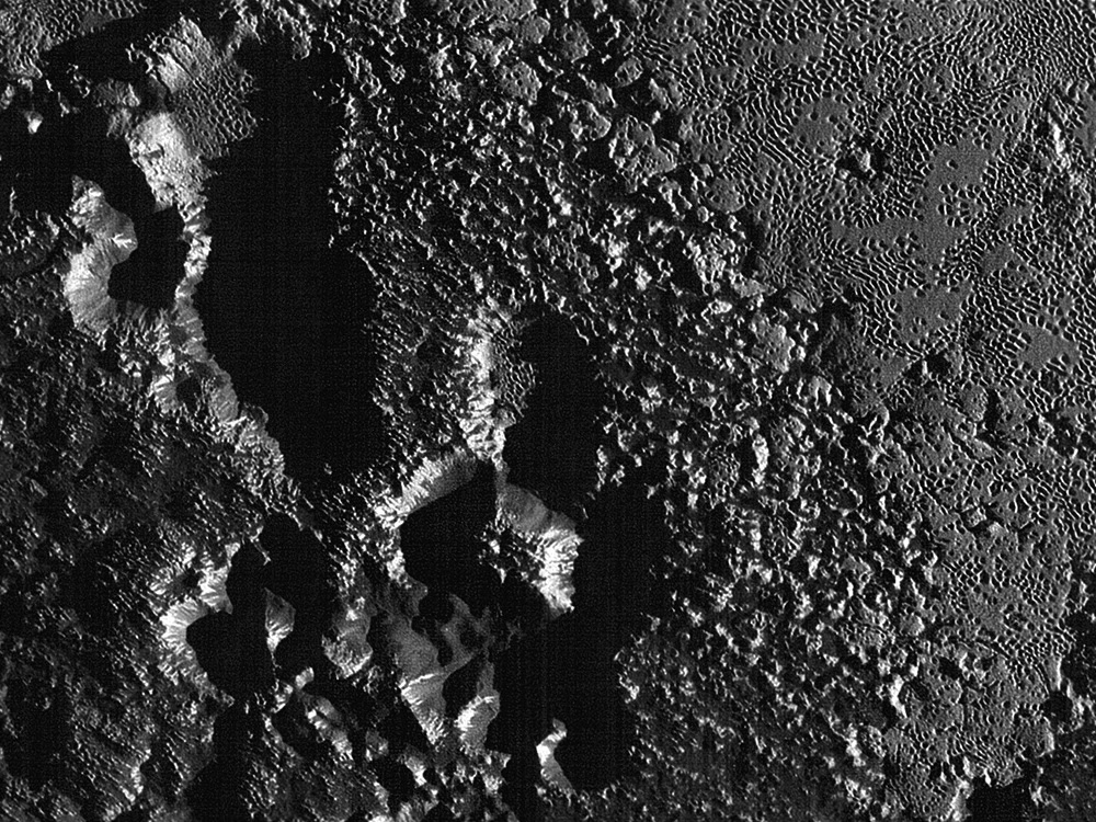 The rugged dark highlands of Pluto as revealed by NASA's New Horizons spacecraft  at 80 metres (260 feet) per pixel during its close flyby of 14 July 2015. Click the image to see the full mosaic strip. Image credit: NASA/JHUAPL/SwRI.