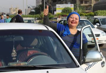 Nour Gaber junto a su taxi en una calle de El Cairo