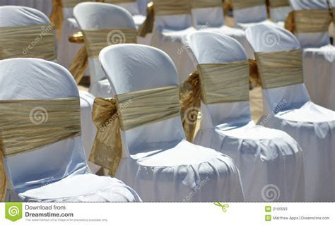 White Chairs With Gold Ribbon At A Beach Wedding Stock