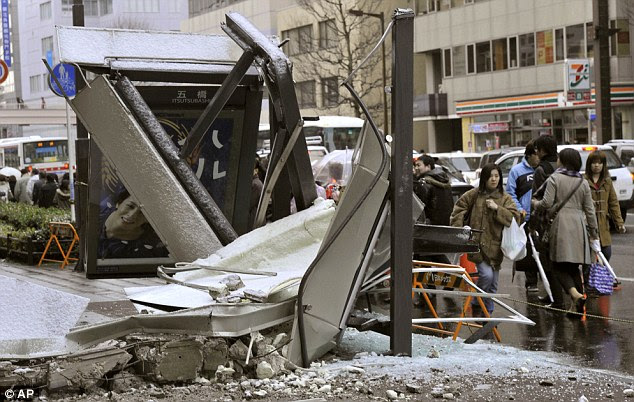 Stunned residents walk past a crushed bus stop which was destroyed by part of a fallen outer wall of a nearby building in Sendai, Miyagi