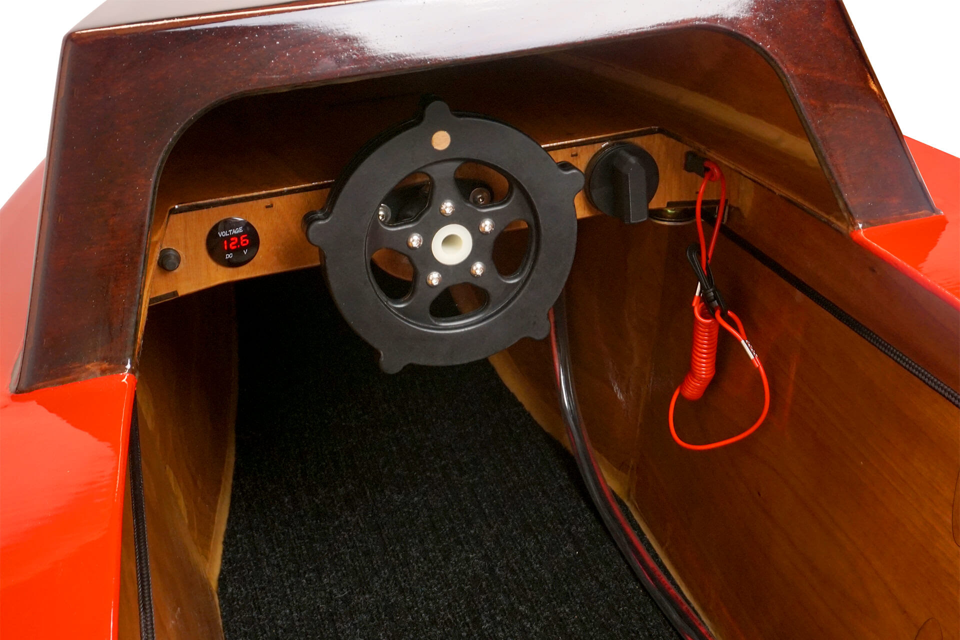 A dashboard view of the mini electric boat, showing off the steering wheel, volt-meter, and dead-mans switch