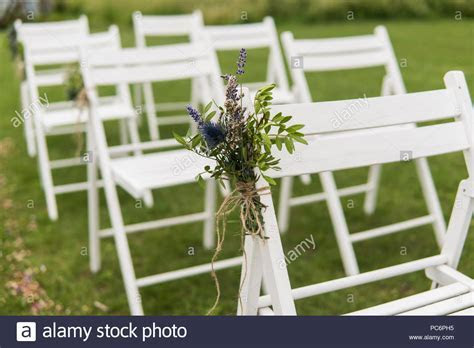 White wedding chairs decorated with fresh flowers on a