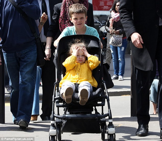 Brotherly love: Cruz Beckham pushed his young sister Harper through Paris on Saturday, followed by Victoria and Romeo