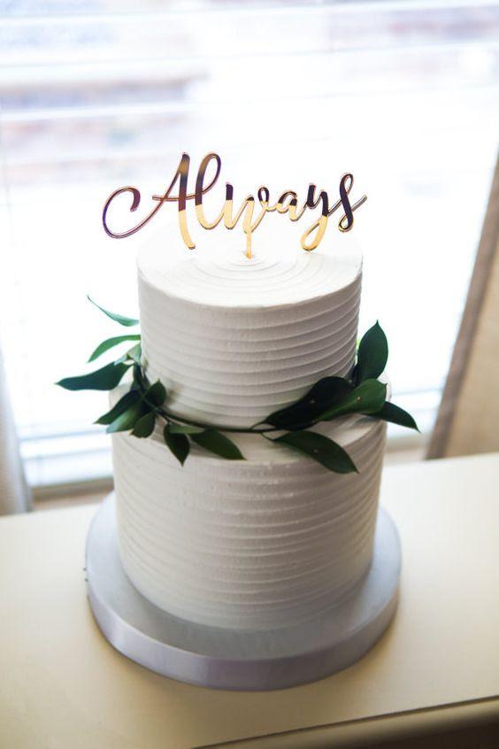 eine weiße textur Hochzeitstorte garniert mit grün und eine Immer topper