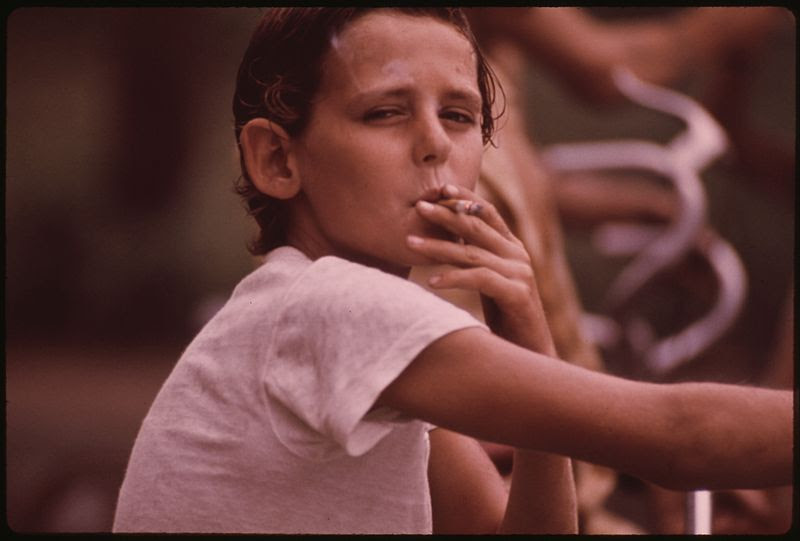 File:DONNY, A NEIGHBORHOOD YOUNGSTER, DRAGS ON A CIGARETTE PASSED TO HIM BY AN OLDER BOY - NARA - 553505.jpg