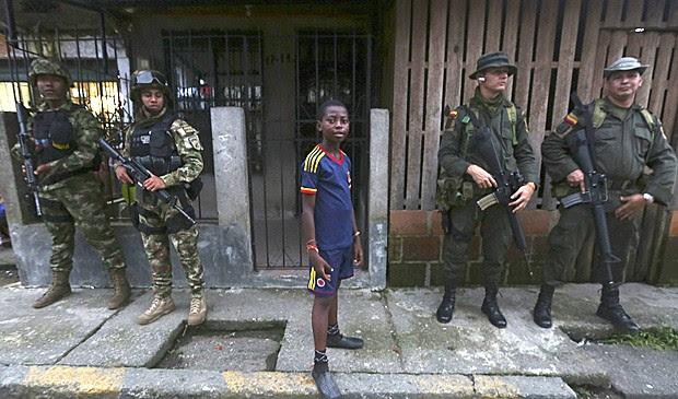 Menino ao lado das Forças Especiais colombianas no bairro de 'La Playita', em Boaventura, durante a visita do ministro da Defesa, Juan Carlos Pinzón. A Human Rights Watch instou autoridades a reforçar a segurança na cidade. (Foto: John Vizcaino/ Reuters)