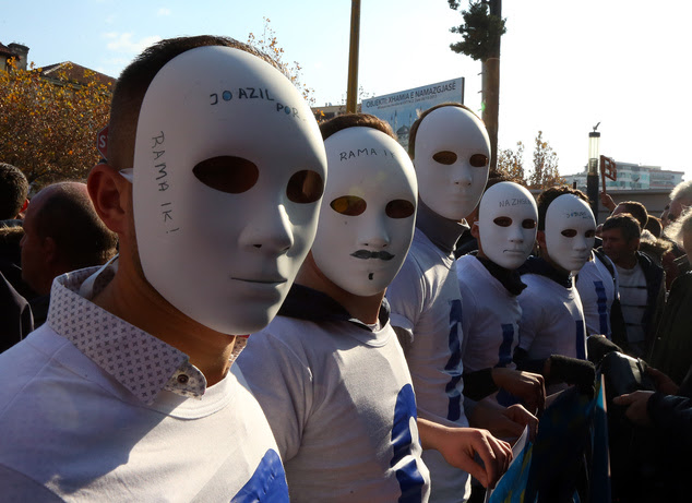 A group of Albanian opposition Democratic Party supporters wear masks during a rally in front of the Parliament building, in Tirana, Albania, Thursday, Dec. ...