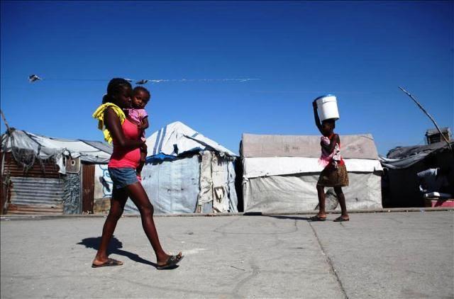 Dos mujeres caminan en el campamento de refugiados Aviación, en Puerto Príncipe (Haití). EFE/Archivo
