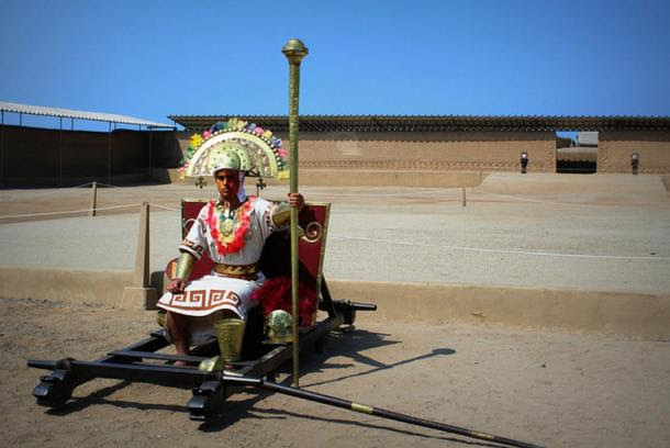 A man dressed as a Chimu elite or priest among the ruins of Chan Chan, Peru.