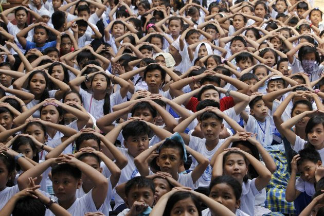 Students cover their heads after evacuating their school building during an earthquake drill at the Baclaran Elementary School Unit-1 in Paranaque city, metro Manila June 7, 2013. Earlier this month, a magnitude-5.7 quake hit Cotabato, southern Philippines, causing damage to several houses and schools and forcing many students to miss the first week of school, local media reported.      REUTERS/Romeo Ranoco  (PHILIPPINES - Tags: EDUCATION SOCIETY)