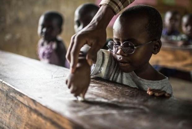 """É o primeiro dia de aula de Criscent. Ele nunca havia visto as letras e precisa aprender o alfabeto do zero. """"riscent perdeu muitos anos de aprendizagem e seu cérebro agora precisa colocar-se em dia com o que vê"""", disse Magyezi. (Foto: Tommy Trenchard / Sightsavers)"""