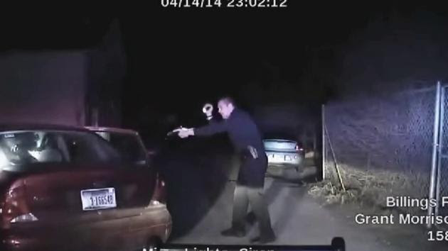 Billings Police Officer Grant Morrison aims a gun into a red sedan on April 14, 2014.