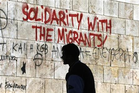 A man walks past graffiti outside the Athens' Academy in central Athens December 6, 2012. A major gateway for Asian and African immigrants trying to enter Europe through its porous borders, Greece has long struggled with illegal immigration. In the last few years, the problem has exploded into a full-blown crisis as Greece sank into a deep recession, leaving one in four jobless and hardening attitudes towards migrants who were blamed for a rise in crime. REUTERS-Yannis Behrakis