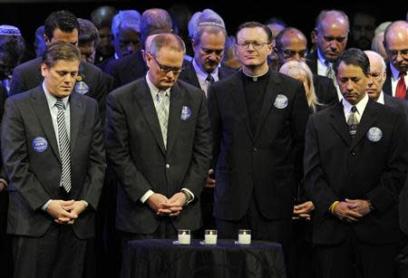 """Rev. Hamilton raises his head after area religious leaders lit """"Candles of Hope"""" during a memorial service at the Jewish Community Center in..."""