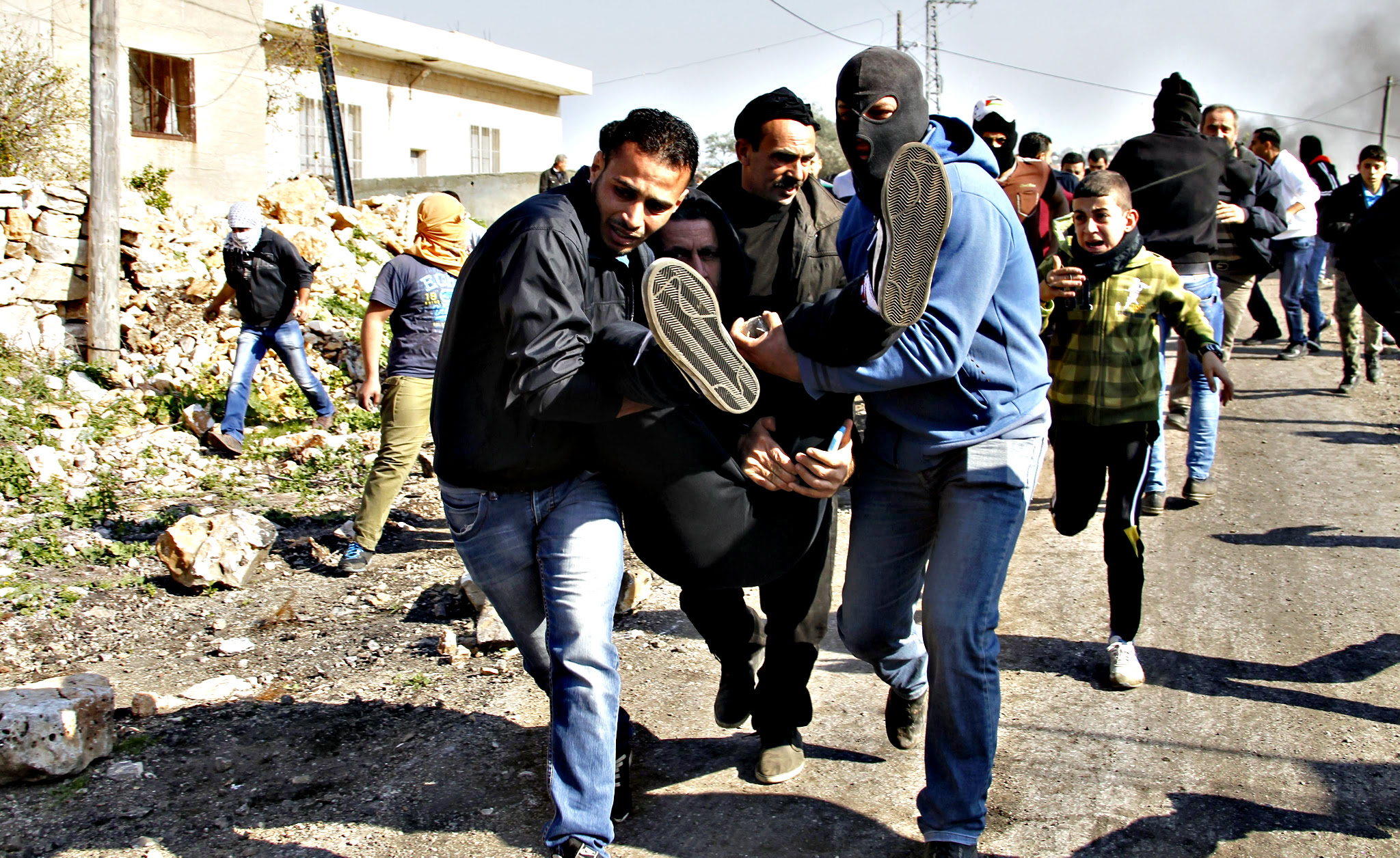 Palestinian protesters carry an injured comrade during clashes with Israeli soldiers that followed a protest against the Israeli settlements in Qadomem, in the Kofr Qadom village near the West Bank city of Nablus, 11 December 2015. According to local sources at least five Palestinians were injured during the clashes.