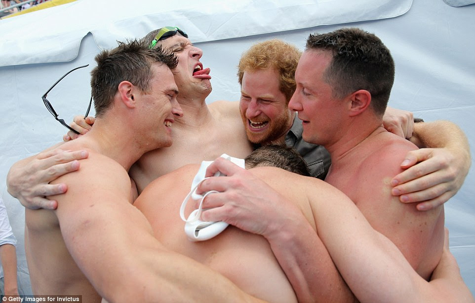 Prince Harry was left rather wet today after David Wiseman and the remainder of the relay swimming team in a celebratory group hug following their triumphant win