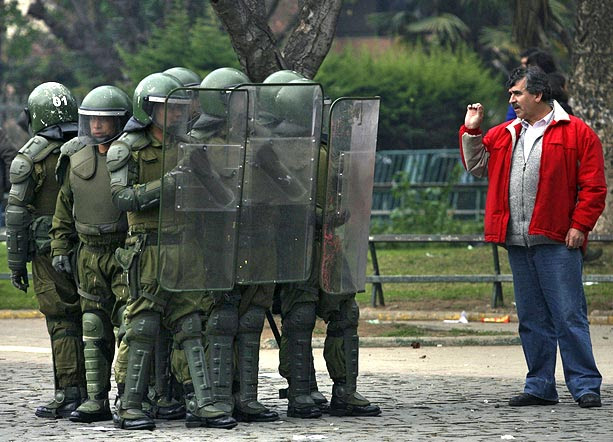 A demonstrator talks to riot police during a rally against proposed education reforms, in Valparaiso, Chile