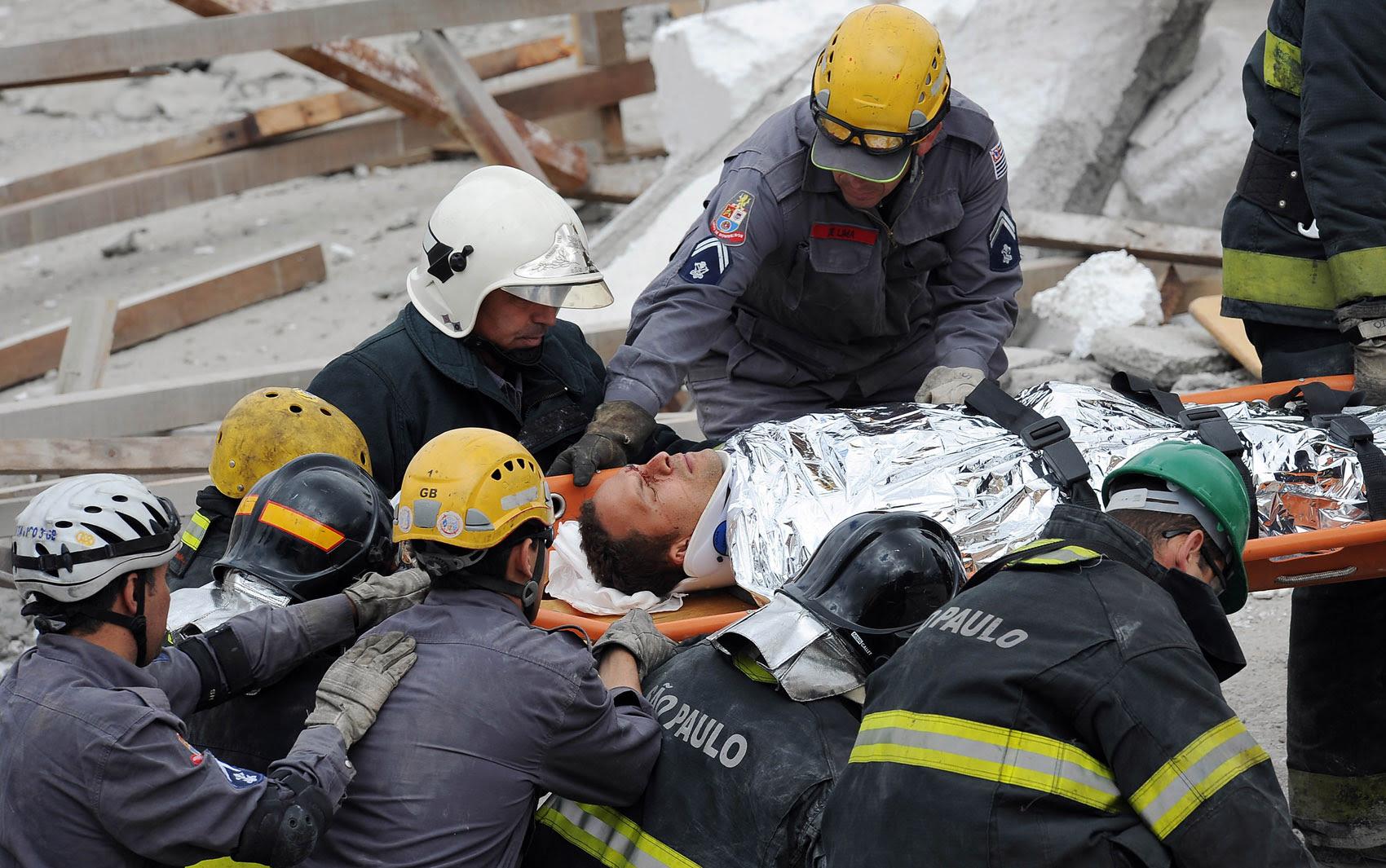 Bombeiros retiram homem ferido dos escombros do desabamento em São Paulo.