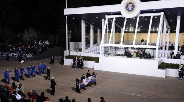 President Obama and his wife Michelle look on from within the reviewing stand as the space shuttle astronauts of flight STS-126 march down Pennsylvania Avenue.