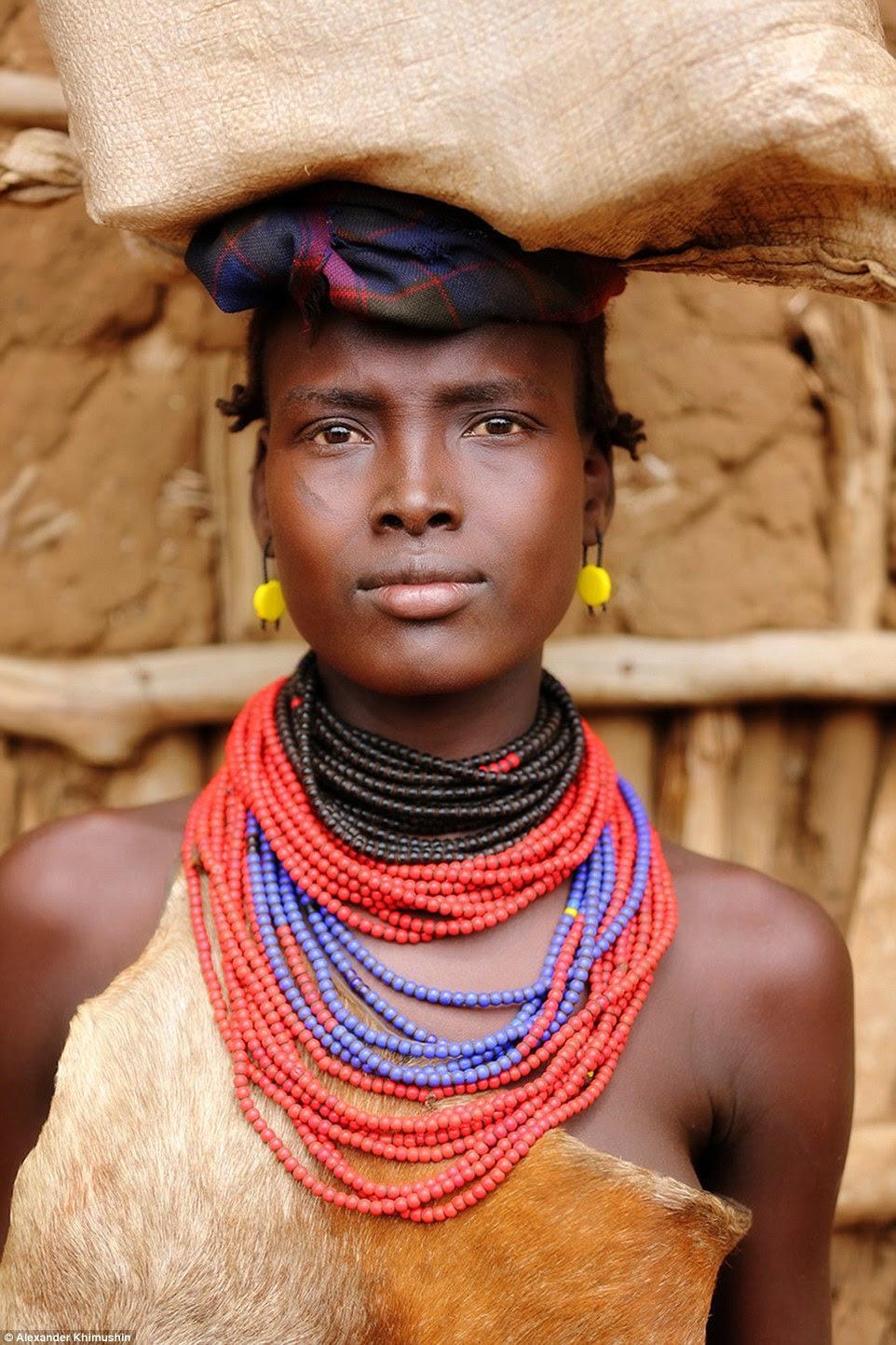 Uma menina tribo Daasanach vestindo um top de peles de animais e um colar de uma série de contas vermelhas, azul e preto carrega um pacote em sua cabeça
