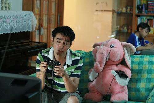 Dad (Chye Chee Keong) playing PS2 with Pinky the Pink Elephant