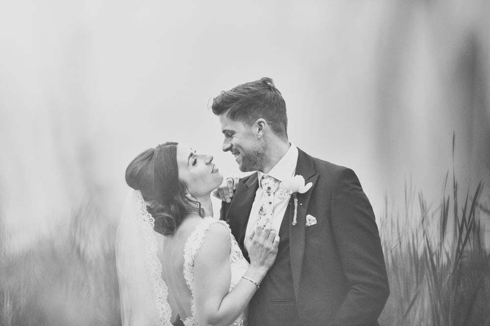 Black & white vingage wedding photo shot through grass in meadow at Moreves Barn in Sudbury Suffolk - www.helloromance.co.uk