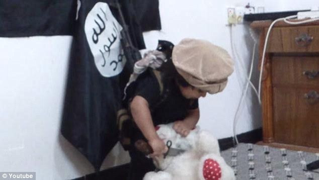 Young militant: The video shows the boy stood in front of two black and white ISIS flags hanging on the bedroom wall as he plunges his blade into the red and white teddy bear