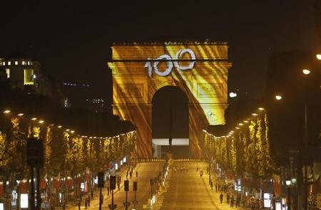 The Arc de Triomphe and the Champs Elysees Avenue are illuminated with the colour of Tour de France winner yellow jersey after the 133.5km final stage of the centenary Tour de France cycling race from