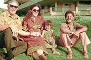 Right to left:A young boy possibly in his early teens, a younger girl (about age 5), a grown woman and an elderly man, sit on a lawn wearing contemporary circa-1970 attire. The adults wear sunglasses and the boy wears sandals.