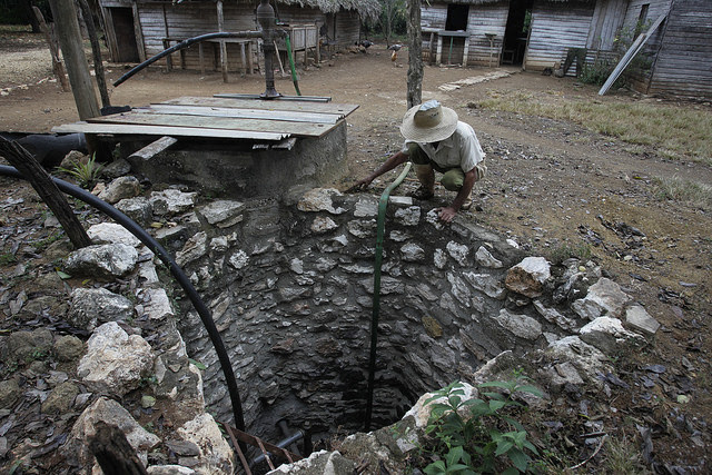 A peasant farmer checks the water level in his backyard well, in the municipality of Horno de Guisa, Granma province, in eastern Cuba. Credit: Jorge Luis Baños/IPS