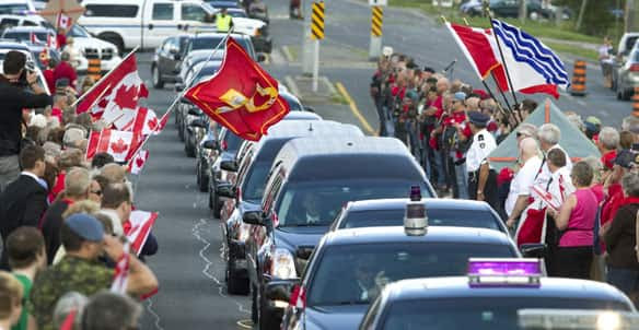 Canadians pay tribute to Master Cpl. Kristal Giesebrecht and Pte.  Andrew Miller as the motorcade carrying their bodies travels from CFB  Trenton to Toronto on Tuesday.