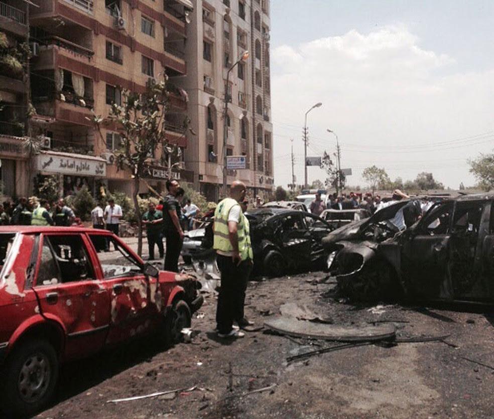 Foto de arquivo mostra quipes de emergência inspecionando local de explosão que atingiu o comboio do procurador-geral do Egito no Cairo (Foto: Ahmed Hatem/AP)
