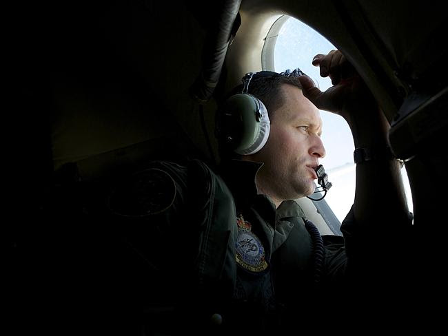 Fighting fatigue...A RAAF crew member looks out of his observation window while searching