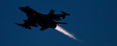An F-16 jet fighter flies over the NATO airbase in Aviano, Italy, Sunday, March 20, 2011. (AP Photo/Luca Bruno)