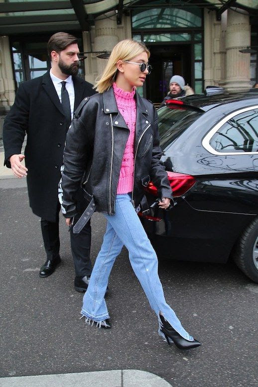 Le Fashion Blog Hailey Baldwin Celeb Style Sunglasses Oversized Biker Jacket Pink Chunky Sweater Light Wash Bell Bottom Side Slit Jeans Black Boots Via Vogue