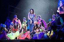 A group of performers on a stage. The women are wearing colorful bustier and skirts and are sitting, while the men are standing behind them. Central to them is a woman wearing a blue, sparkling costume.