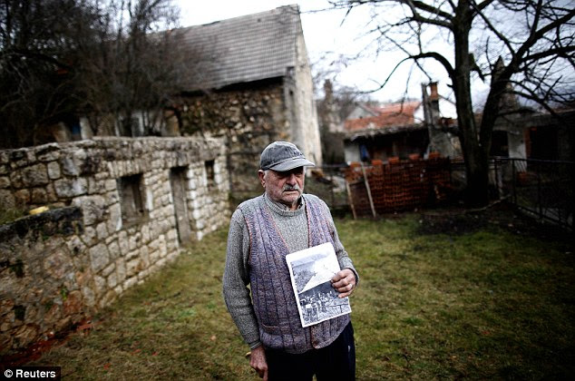 Miljkan Princip, the grandson of Gavrilo Princip's brother, poses with a photo of the assassin's old house as he stands in front of it in Bosansko Grahovo