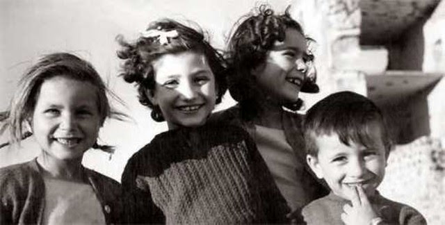 Niños sonríen junto a las ruinas del Alcázar de Toledo en 1953. Fotografía de Ira H. Latour. Carl Mautz Vintage Photographs