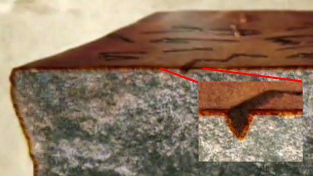 Pedra com pátina e detalhe das letras