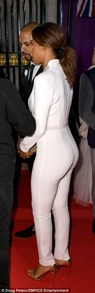 Looking good: The former Saturdays singer, 28, flashed a peek of sideboob as she went braless at London's Grosvenor House in a chic tailored ivory catsuit with a perilously plunging neckline
