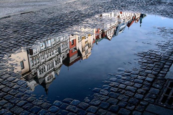 Отражение домов в луже. Фото