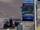 Probe: An armed police officer stands by the megabus coach on the M6 toll road