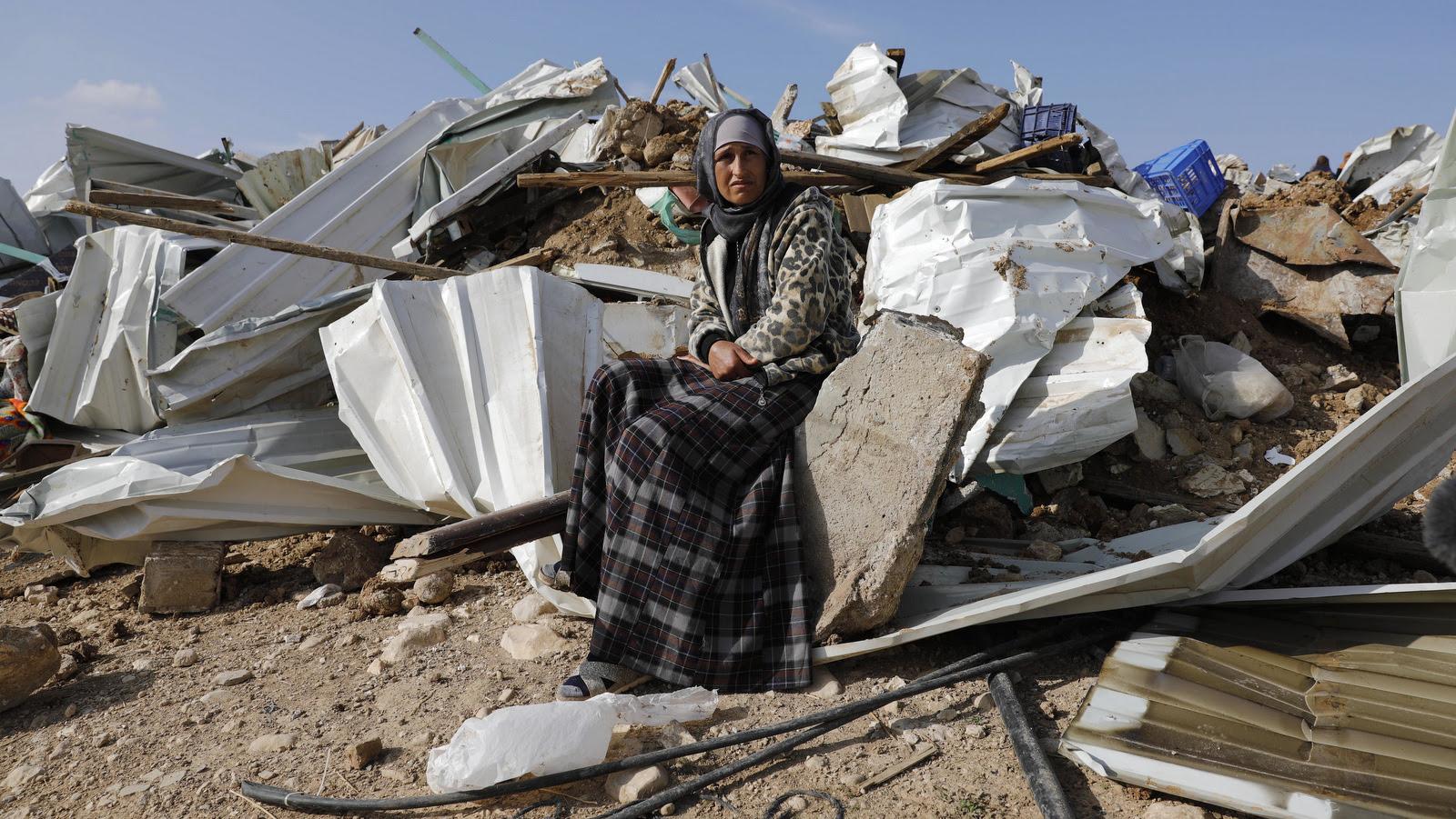 Uma mulher beduína se sente sobre os restos da sua casa demolida na aldeia beduína de Umm al-Hiran, perto da cidade do sul de Beersheba, Israel, 18 de janeiro de 2017. (AP / Tsafrir Abayov)