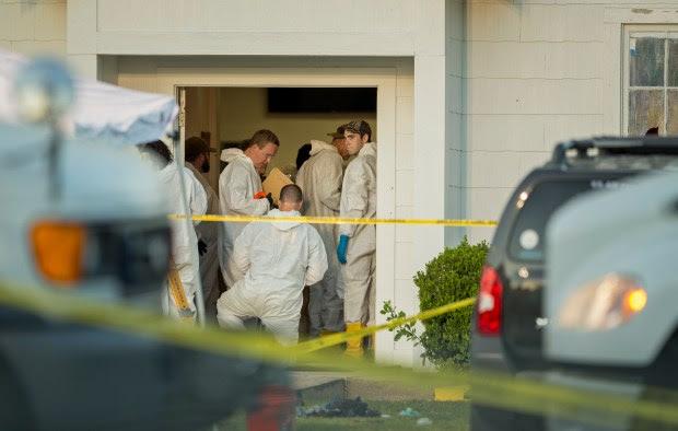 Investigators work at the scene of ...