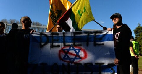 Demonstrators carry a defaced Israeli flag during a rally to mark Al-Quds day on the last Friday of the holy month of Ramadan - Photo via Press TV